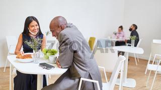 Geschäftsleute sitzen an getrennten Tischen in der Cafeteria