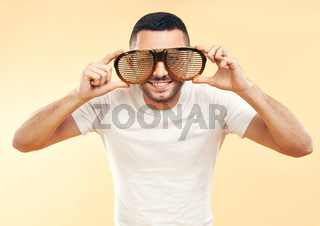 Young man in funny party glasses over yellow background
