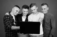 Four young handsome men together against gray background