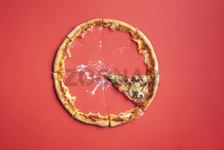 Single slice of pizza and crumbs on a red background