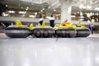 The curling stone or rock is made of granite with yellow handles lie