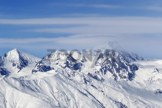 High snowy mountains and blue sky with clouds