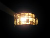 Shinning lighthouse lamp. Fresnel lens made from glass rings. Closeup night view