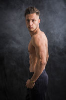 Handsome shirtless athletic young man in studio shot