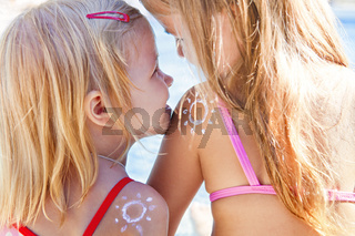 Portrait of the happy blond haired girls sisters with cream on the sholders in shape of sun laughing and hug in sunset