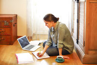 Woman designer using laptop on floor