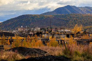 The nature of the Magadan region. An abandoned gold mining enterprise in the tundra of Russia. Abandoned mine buildings in the mountains