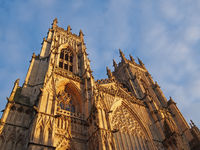 a front view of the towers at the entrance to york minster in sunlight against a blue cloudy sky