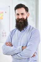 Portrait of a happy smiling bearded senior developer or manager in modern IT office.