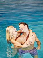 Paar lacht im Pool im Sommer