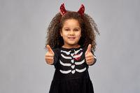 girl in black dress and devil's horns on halloween