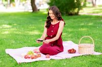 happy woman with smartphone on picnic at park