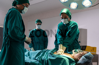 Surgeon and nurse do CPR to patient.