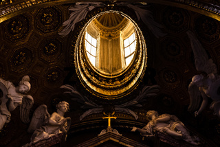 Skylight guarded by statues of angels in a church in Rome