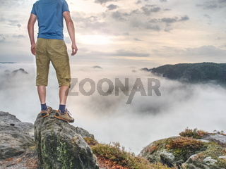 Hiker in middle of nowhere and thinking alone. Man sit on top