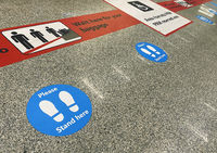 Stickers on the floor near the baggage claim belt at the airport that warn of keeping social distanc