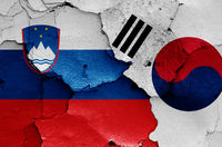 flags of Slovenia and South Korea painted on cracked wall