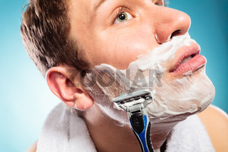 Handsome man shaving with razor