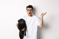 Image of confused hipster man holding dog and shrugging, dont know, raising hand puzzled, standing with his animal over white background