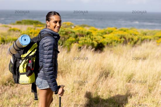 Portrait of fit african american woman wearing backpack nordic walking on coast