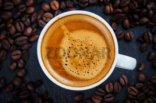 Cup of espresso with coffee beans - top view