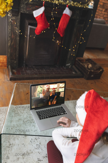 Rear view of woman in santa hat having a videocall with man and son in santa hats waving on laptop a