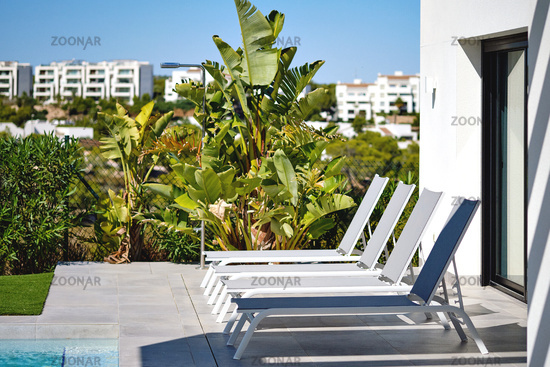 Empty deck chairs near swimming pool