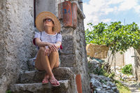 Beautiful female tourist wearing big straw sun hat and shorts sitting and relaxing on old stone house stairs during summer travel on Mediterranean cost on hot summer day