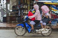 Riding a motor-bike in the rain, Luang Prabang, Laos