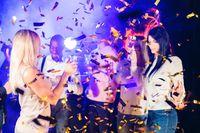 Happy people dance in confetti