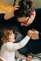 Father with child on the couch. Cozy home activity with child. fatherhood