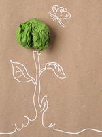 Recycled paper background with green crumpled paper ball as flower, ecology concept, innovations, new ideas