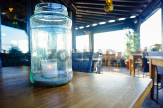 An illuminated candle in the glass jar on table