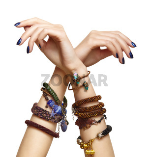 Female hands with handmaid bijouterie bracelets. Nails with blue manicure