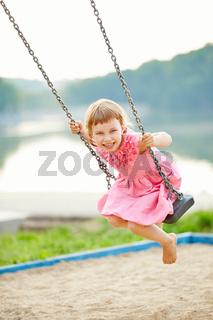 Lachendes Mädchen schaukelt im Sommer