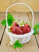 Strawberries in basket with flowers and leaves on board