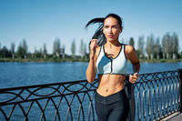 Young fitness woman runner running at riverside