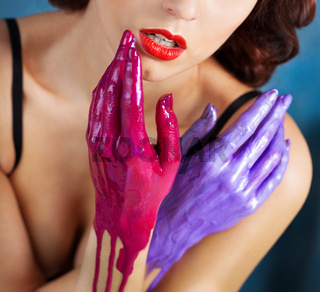 Beautiful young woman with colored splashes hands