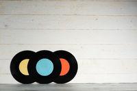 Three Vinyl records on wooden background