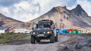 Four-wheel drive vehicles Nissan Patrol driving on mountain road on background volcano landscape. Active vacation, off-road trip in travel destinations
