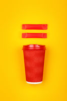 Red paper coffee cup over yellow