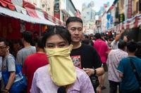 Singapur, Republik Singapur, Frau mit Mundschutz auf einem belebten Basar in Chinatown