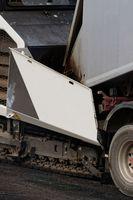 Asphalt paver loading new asphalt