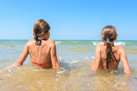 Children sit in the water on the coast and look into the distance