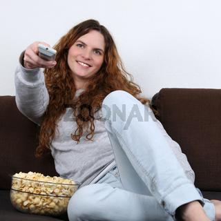Junge Frau schaut fernsehen und isst Popcorn