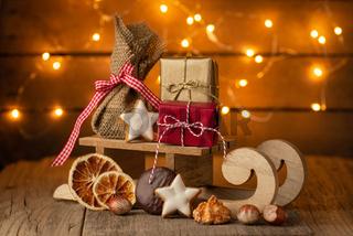 Leuchtendes Weihnachten - Holzschlitten mit Päckchen und Lichtern