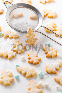 Homemade Christmas cookies in Christmas tree shape on marble background