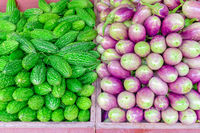 Vibrant green bitter melon and purple Asian eggplants at vegetable stand in Little India, Singapore