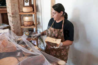 Vendor serving variety of traditional cheese in a cheese farm store