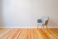 chair in empty flat with wooden floor and grey wall copy space background -